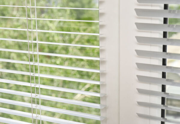 Window with open modern horizontal blinds indoors, closeup